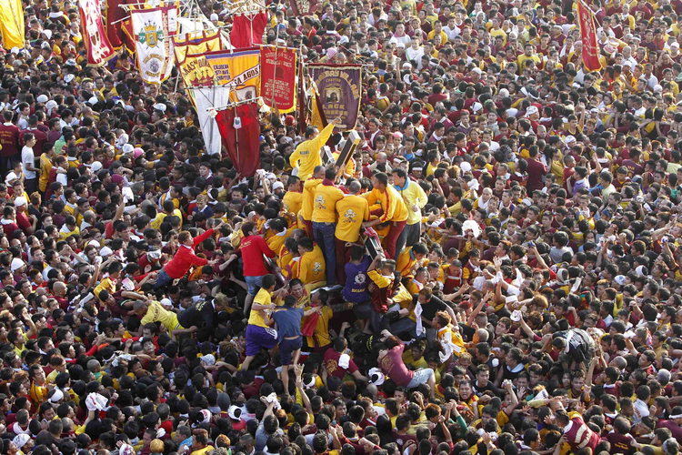 Pilgrims climb to touch statue of Black Nazarene during procession in Manila. (CNS photo/Romeo Ranoco, Reuters)