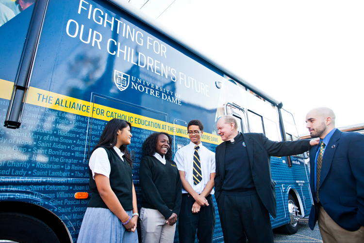 Stundets from Cristo Rey Jesuit High School in Baltimore talk with Holy Cross Father Timothy Scully from the University of Notre Dame and Cristo Rey teacher Lee Imbriano.