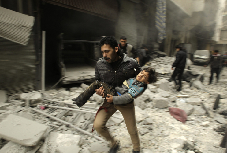 A man runs while carrying a child who survived what activists say was an airstrike by forces loyal to Syrian President Bashar Assad in Aleppo Jan. 21. (CNS photo/Ammar Abdullah, Reuters)