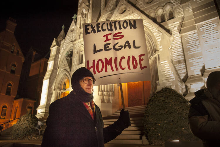 Man holds sign at vigil outside St. Louis University College Church ahead of execution of death-row inmate.
