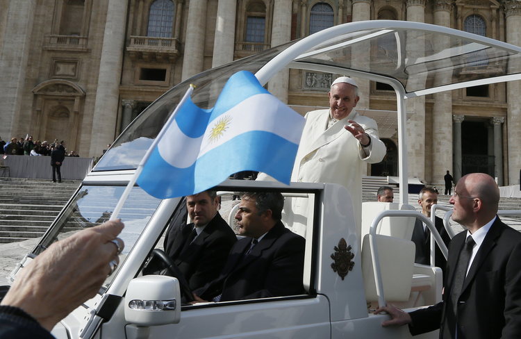 Pilgrim waves Argentina's flag as Pope Francis leaves general audience in St. Peter's Square at Vatican. (CNS photo/Paul Haring)