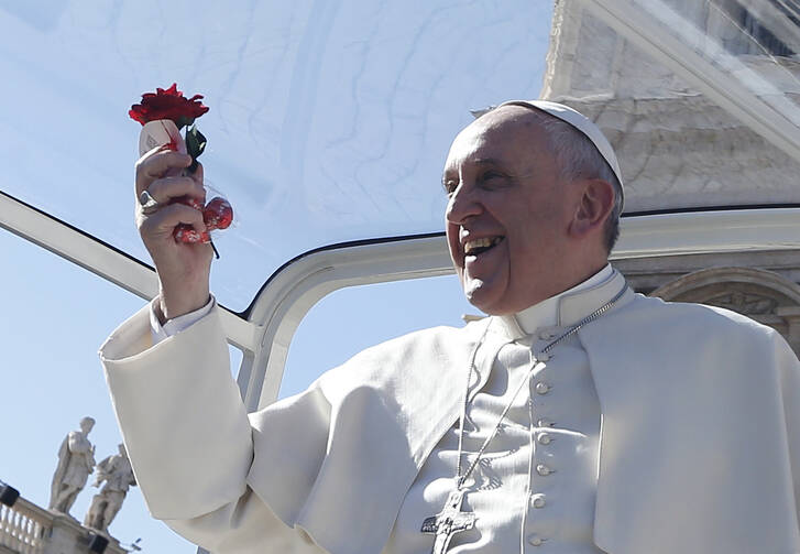 Pope Francis holds a rose and chocolates thrown by a person in the crowd as he arrives for an audience for engaged couples in St. Peter's Square at the Vatican Feb. 14, Valentine's Day. (CNS photo/Paul Haring)