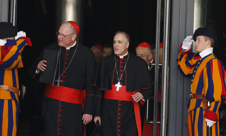 Swiss Guards salute as Cardinals Timothy M. Dolan of New York and Daniel N. DiNardo of Galveston-Houston leave a meeting of cardinals with Pope Francis in the synod hall at the Vatican Feb. 21, 2014. (CNS photo/Paul Haring)