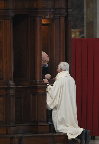 Priest hears confession of clergy member in St. Peter's Basilica at Vatican. (CNS photo/Paul Haring)