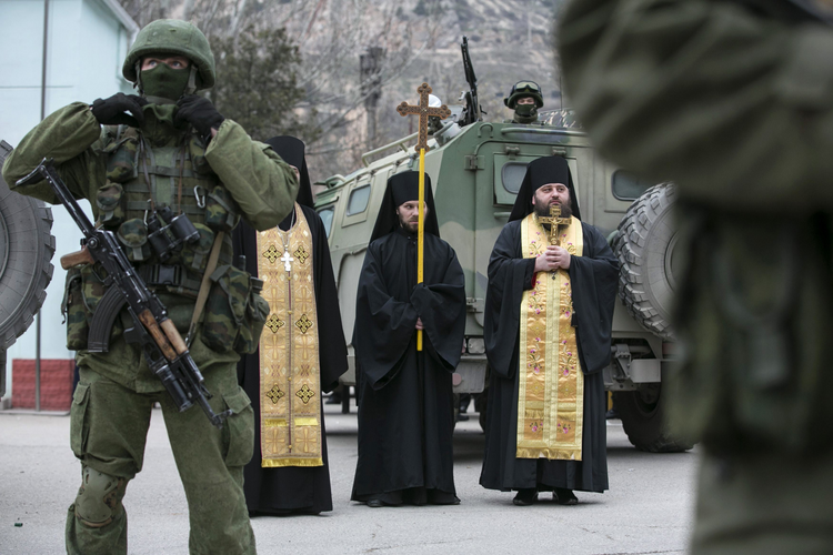 Orthodox clergymen pray near armed servicemen outside Ukrainian border guard post. (CNS photo/Baz Ratner, Reuters)