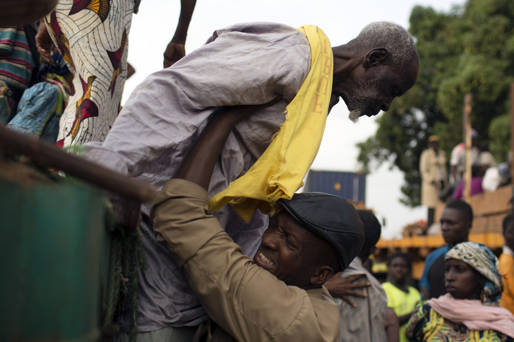 Priest helps a Muslim man climb down from an open truck in Central Africa Republic. (CNS photo/Siegfried Modola, Reuters)