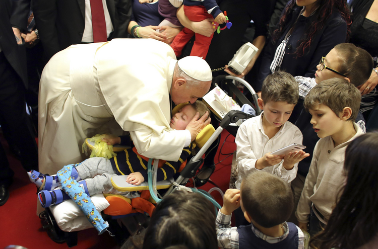 Pope Francis kisses a disabled child during a visit to the parish of Santa Maria dell'Orazione on the outskirts of Rome March 16. (CNS photo/Stefano Rellandini, pool via Reuters)