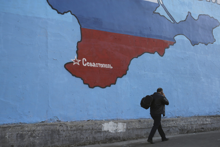 A man passes a mural showing a map of Crimea in Russian national colors on a street in Moscow. (CNS photo/Artur Bai nozarov, Reuters)