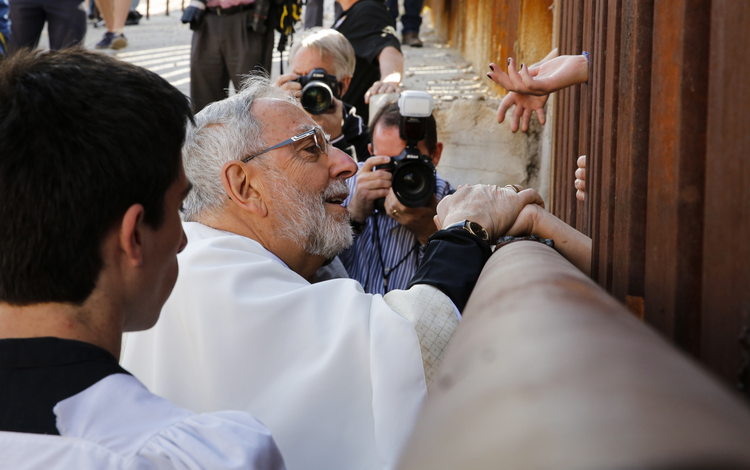 U.S. Bishop Kicanas blesses people as he distributes Communion through border fence in Nogales, Ariz.