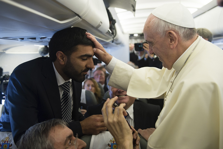 Pope Francis blesses journalist aboard papal flight en route to Amman. (CNS photo/L'Osservatore Romano via Reuters)