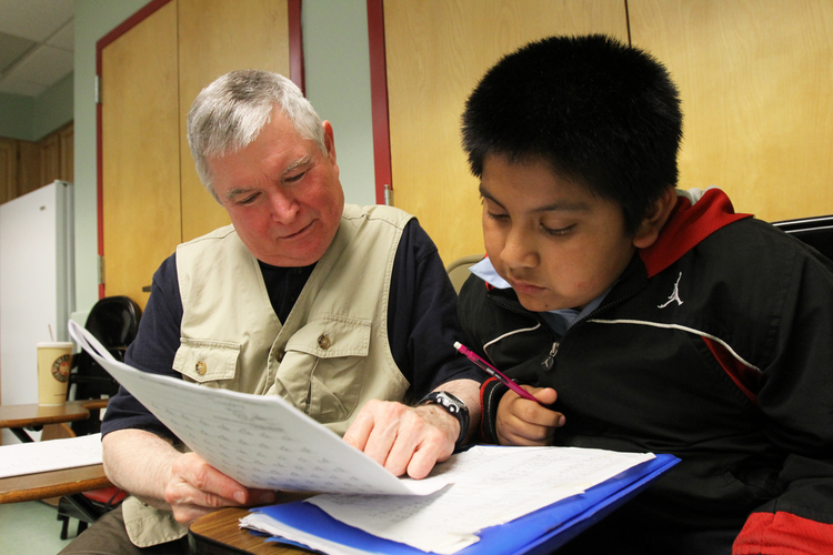 Member of Ignatian Volunteer Corps tutors boy during after-school program at Mercy Center in New York.