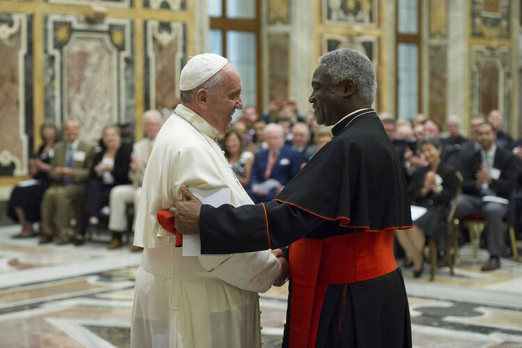 Pope Francis shakes hands with Ghanaian Cardinal Peter Turkson, president of the Pontifical Council for Justice and Peace, during a meeting with council members at the Vatican June 16. (CNS photo/L'Osservatore Romano via Reuters)