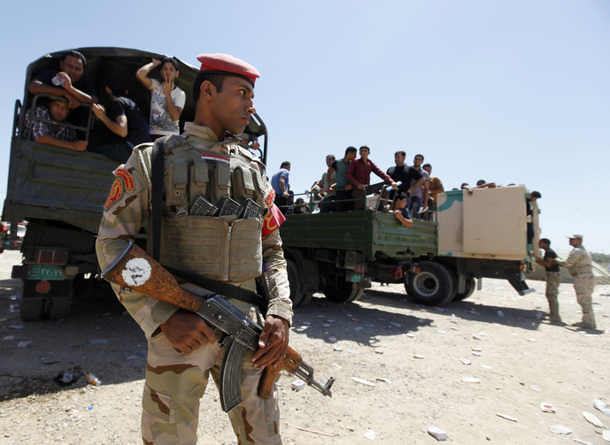 Member of Iraqi security forces stands guard in front of army volunteers. (CNS photo/Ahmed Saad, Reuters)