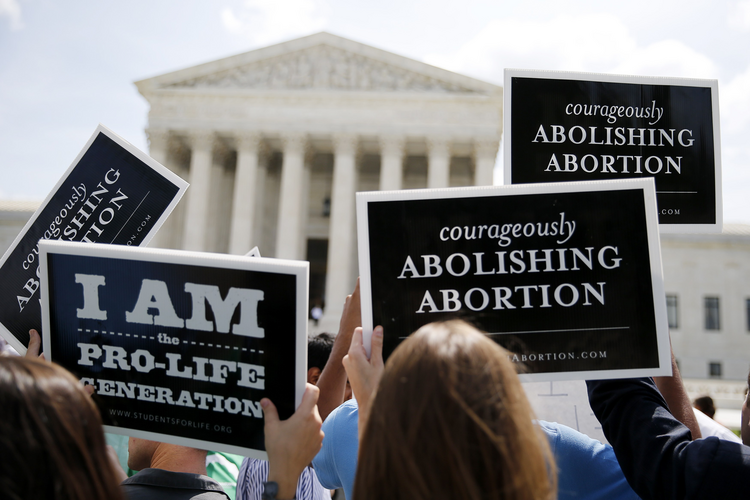 Pro-life supporters hold up signs as they celebrate U.S. Supreme Court ruling striking down buffer zones around abortion clinics. (CNS photo/Jim Bourg, Reuters)