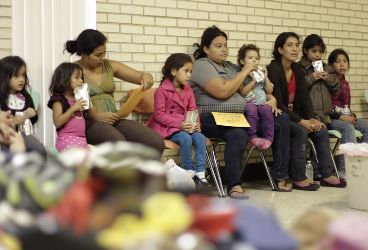 Migrants sit in shelter at Catholic church in Texas.