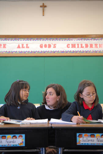 A Jesuit Volunteer Corps teacher assists students at Holy Wisdom Academy in Milwaukee in this 2007 photo. Even with school out for the summer, the debate is ongoing about the love-them-or-hate-them Common Core State Standards, developed by the National Go