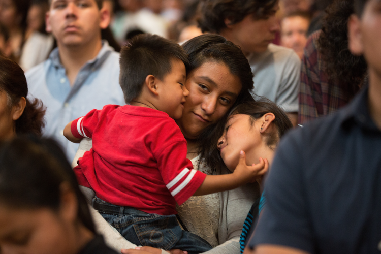 Woman holds onto her children during special Mass in Los Angeles honoring immigrants. (CNS photo/Victor Aleman, Vida-Nueva.com)