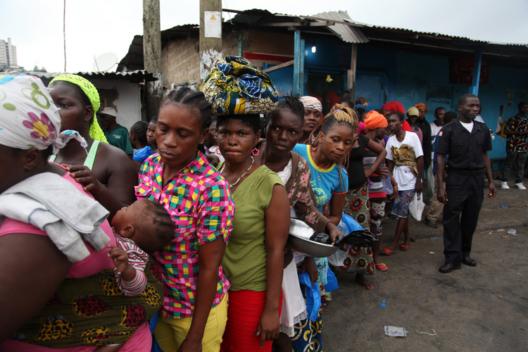 Liberian police control residents in Ebola quarantined area as they wait for food rations. (CNS photo/Ahmed Jallanzo, EPA)