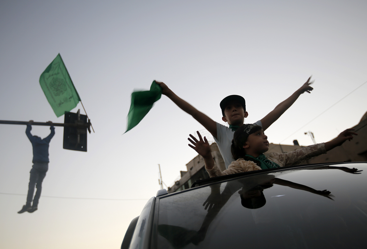 Palestinians celebrate a cease-fire in Gaza City Aug. 26. Catholic aid officials say they hope the Egyptian-brokered Israeli-Hamas cease-fire proposal will hold. (CNS photo/Mohammed Saber, EPA)