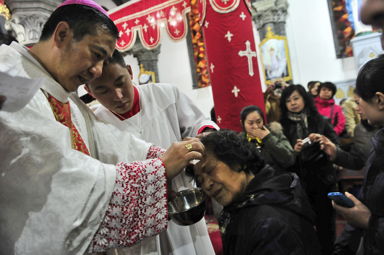 Chinese Catholic priests baptize new believers during a 2013 Easter Vigil in a church in Shenyang, China. A papal visit to China does not appear likely anytime soon, according to experts on the church in China. (CNS photo/EPA)