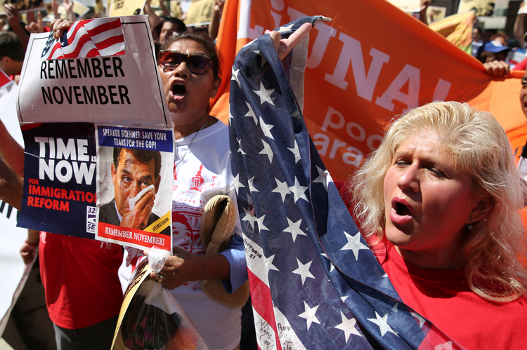 Protesters hold banners and flags during an immigration rally and march outside the U.S. Immigration and Customs Enforcement headquarters in Washington Aug. 28. (CNS photo/Bob Roller)
