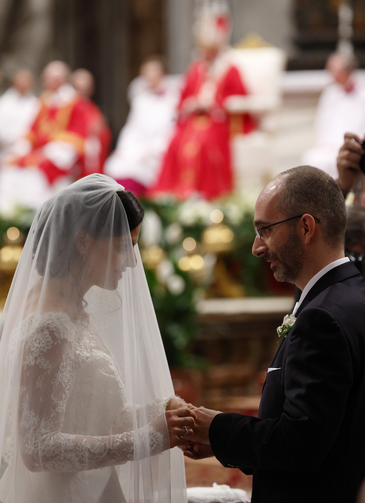 New spouses exchange rings as Pope Francis, pictured in the background, celebrates the marriage rite for 20 couples during a Mass in St. Peter's Basilica at the Vatican Sept. 14. (CNS photo/Paul Haring)