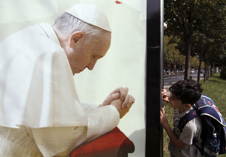 A boy looks at a poster of Pope Francis in Tirana, Albania, Sept.19. The pope will be making a day trip to Albania Sept. 21. (CNS photo/Arben Celi, Reuters)