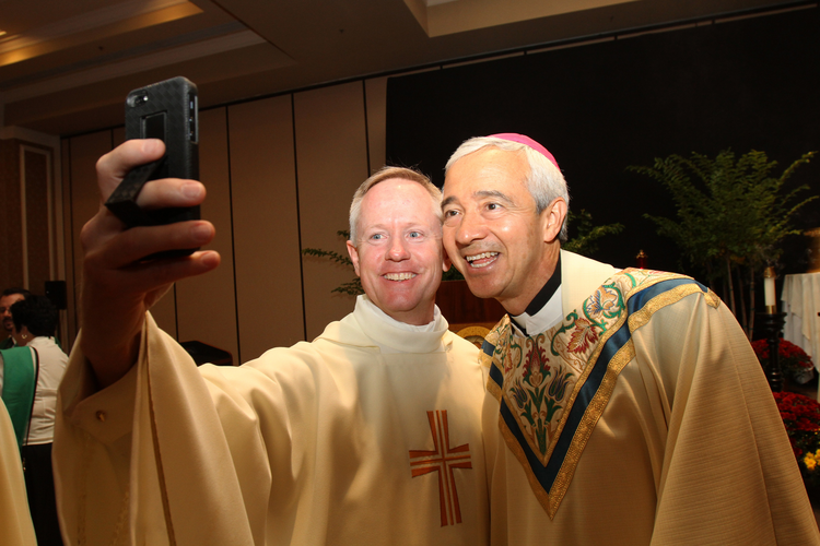 Vatican official, Denver archdiocesan vocations director pose for selfie during vocation conference. (CNS photo/Gregory A. Shemitz)