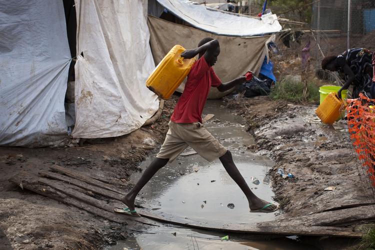 South Sudanese boy fetches water in displaced person camp.