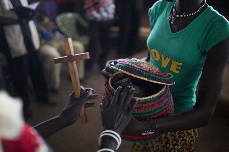 South Sudanese woman gives alms during Mass in camp for displaced people. (CNS photo/Jim Lopez, EPA)