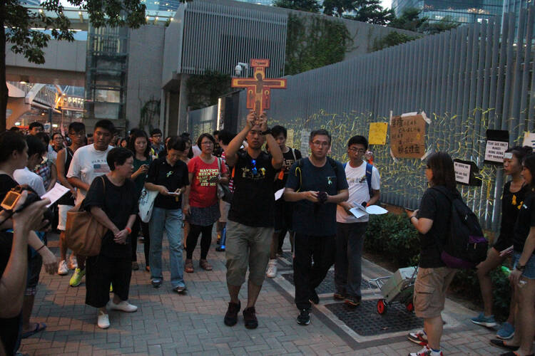 About 100 Catholic youths pray for democracy outside Hong Kong's government headquarters building Sept. 30.  (CNS photo/Francis Wong)