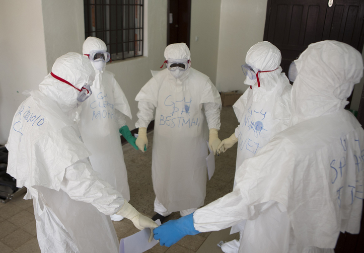Health workers wearing protective equipment pray at start of shift before entering Ebola treatment center in Liberia. (CNS photo/Christopher Black, WHO, Handout via Reuters)