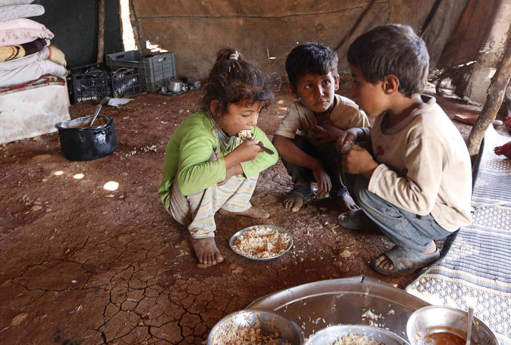 Internally displaced children eat inside a tent in Aleppo, Syria, Oct. 8, 2014. (CNS photo/Jalal Al-Mamo, Reuters)