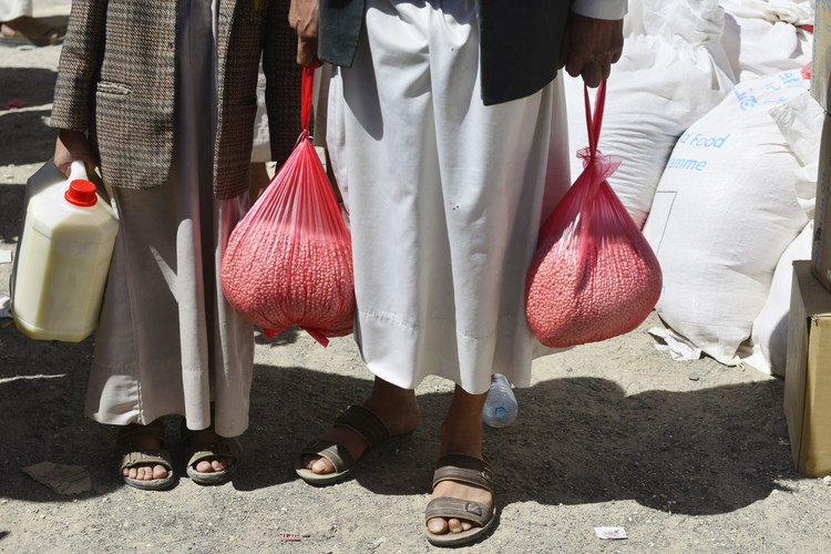 Yemenis receive food at a distribution center in Sana'a, Yemen earlier this year.