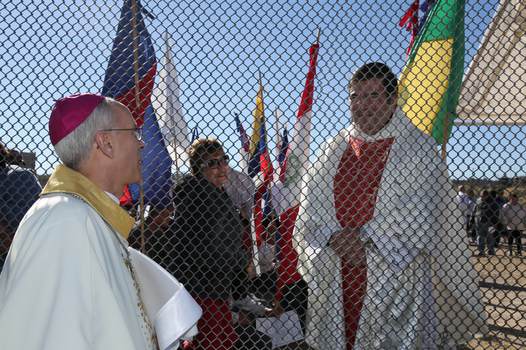 Bishop Mark J. Seitz of El Paso, Texas, right, talks through the border fence to Msgr. Jose Rene Planco of Juarez, Mexico, before a Mass Nov. 22 in Sunland Park, N.M., at the Mexican border. (CNS photo/Bob Roller)