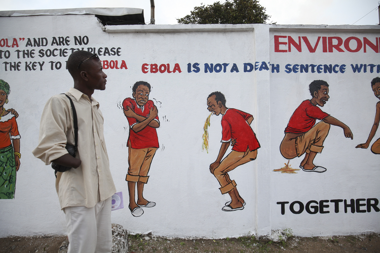 Liberian man looks at an Ebola sensitization campaign painted on a wall in downtown Monrovia.