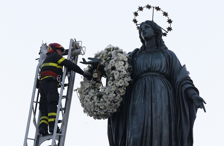 A firefighter places a wreath at the foot of a tall statue of Mary overlooking the Spanish Steps in Rome Dec. 8, the feast of the Immaculate Conception. Rome's firefighters have observed the tradition every year since 1857. (CNS photo/Paul Haring)