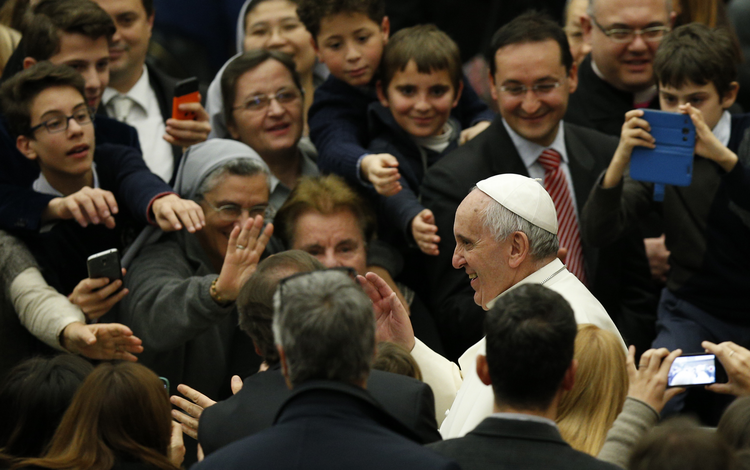Pope Francis greets people as he leaves audience to give Christmas greetings to Vatican employees.