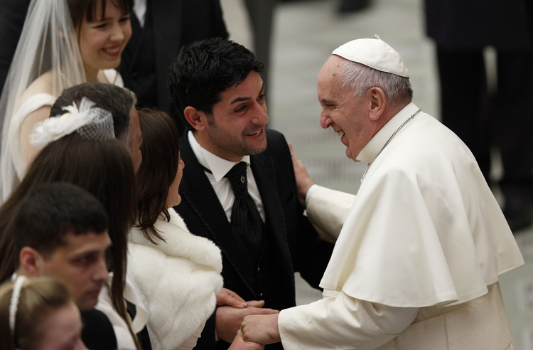 Pope Francis shares a laugh with a newly married couple during his general audience in Paul VI hall at the Vatican Jan. 7. (CNS photo/Paul Haring)