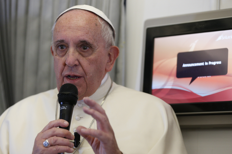 Pope Francis answers questions from the media aboard his flight to Manila, Philippines, Jan. 15. (CNS photo/Paul Haring)