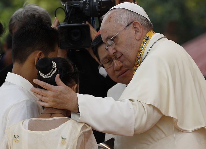 Pope Francis comforts former street child who spoke during meeting with young people at university in Manila.