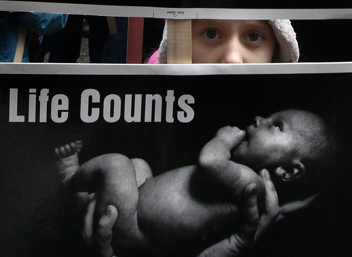A young girl peeks through signs she is holding as she walks through downtown Chicago during the city's Jan. 18 March for Life. The marchers were calling for an end to abortion. (CNS photo/Karen Callaway, Catholic New World)