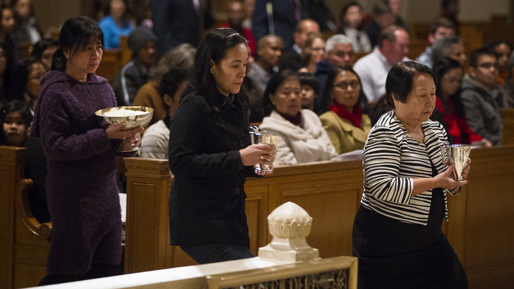 Human trafficking survivors carry offertory gifts to altar at during Mass at national shrine.