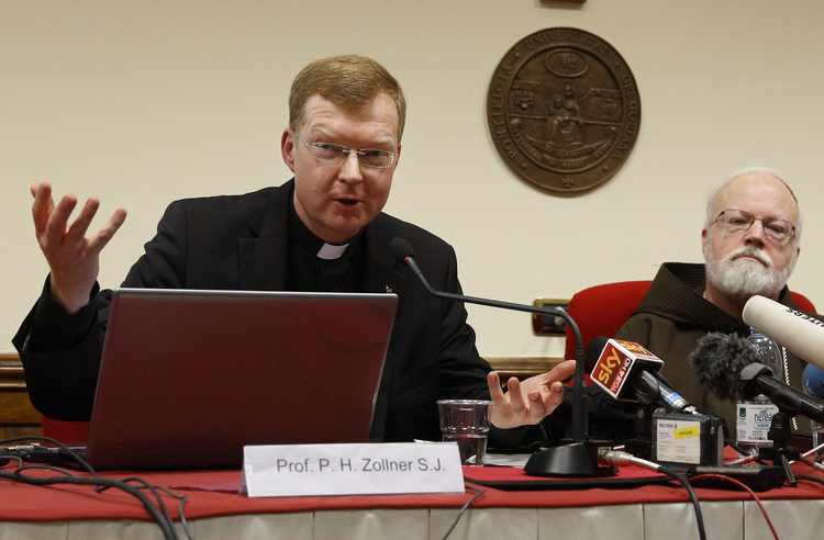 Jesuit Father Hans Zollner, president of the Center for Child Protection at the Pontifical Gregorian University in Rome, speaks at a news conference officially launching the center in February 2015. Also pictured is Cardinal Sean P. O'Malley of Boston, head of the Pontifical Commission for Child Protection. (CNS photo/Paul Haring)