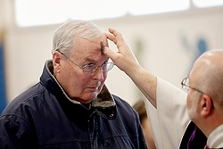 Larry Rodwell receives ashes from Father Paul Bonacci during an Ash Wednesday Mass at St. Pius X Church in Rochester, N.Y., Feb. 18. Ash Wednesday marks the start of Lent. (CNS photo/Mike Crupi, Catholic Courier)