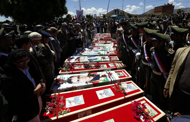 Yemeni mourners gather beside coffins of recent suicide attacks.
