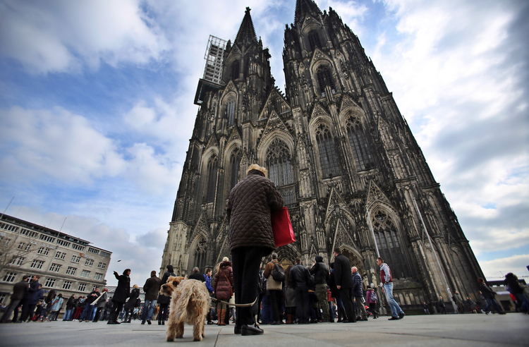 People stand during a moment of silence for the victims of the Germanwings flight crash in front of the Cologne Cathedral in Cologne, Germany, March 26. (CNS photo/Oliver Berg, EPA)