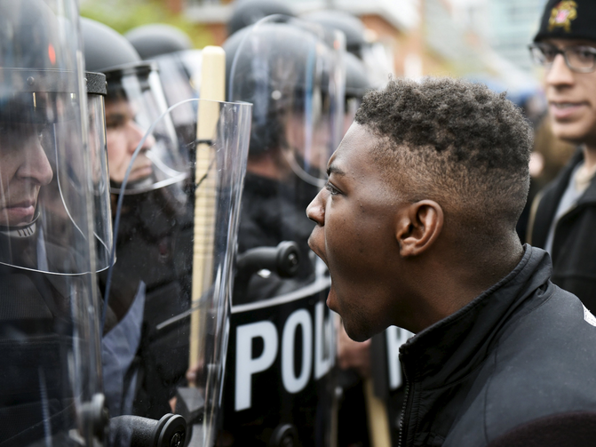 A demonstrator confronts police near Camden Yards during a march to protest the death of Freddie Gray in Baltimore April 25. (CNS photo/Sait Serkan Gurbuz, Reuters)
