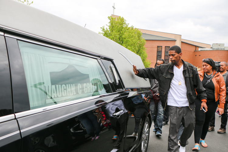 A mourner pats the hearse holding the casket of Freddie Gray outside New Shiloh Baptist Church in West Baltimore on April 27. (CNS photo/Olivia Obineme, Catholic Review)