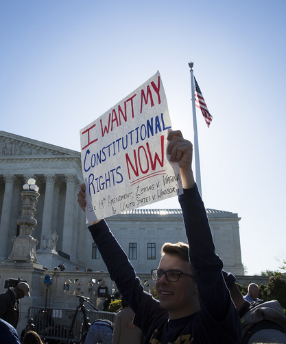 A supporter for same-sex marriage stands outside the U.S. Supreme Court in Washington April 28. The high court began hearing cases for same-sex marriages in states that bar the union. (CNS photo/Tyler Orsburn)
